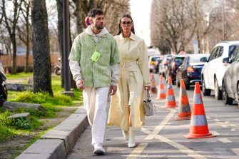 PARIS, FRANCE - JANUARY 18: Jean-Sebastien Rocques (L) wears a  neon-green Jacquemus mini-bag, rings, a cream-color hooded sweatshirt, a pistachio-green short sleeved shirt with white floral embroideries, cream-color pants, white sneakers  ;  Alice Barbier (R) wears earrings, sunglasses, a light yellow trench coat, a Fendi white and grey bucket bag, square-toe white boots, outside Sacai, during Paris Fashion Week - Menswear F/W Fall/Winter 2020-2021 on January 18, 2020 in Paris, France. (Photo by Edward Berthelot/Getty Images)