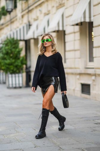 PARIS, FRANCE - APRIL 01: Xenia Adonts wears neon green sunglasses from Chiara Ferragni, a black wool pullover with v-neck from Bazilika, a black short mini shiny leather slit skirt from Rick Owens, a Coperni black leather bag, knee-high lace-up black leather combat boots from Ann Demeulemeester, during a street style fashion photo session, on April 01, 2021 in Paris, France. (Photo by Edward Berthelot/Getty Images)