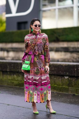 PARIS, FRANCE - MARCH 01: A guest wears a multicolor floral print dress, a green studded bag, green earrings, green pointy shoes, sunglasses, outside Valentino, during Paris Fashion Week - Womenswear Fall/Winter 2020/2021, on March 01, 2020 in Paris, France. (Photo by Edward Berthelot/Getty Images)