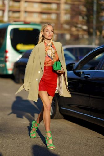 MILAN, ITALY - FEBRUARY 19: Leonie Hanne wears a beige coat, an orange floral print top, a green quilted bag, a red leather skirt, green shoes, outside Alberta Ferretti, during Milan Fashion Week Fall/Winter 2020-2021, on February 19, 2020 in Milan, Italy. (Photo by Edward Berthelot/Getty Images)