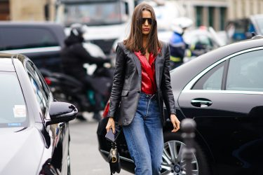 PARIS, FRANCE - FEBRUARY 28: A guest wears sunglasses, a black leather blazer jacket, a red shiny glittering double breasted top, blue denim jeans pants, a Dior Saddle bag, outside Balmain, during Paris Fashion Week - Womenswear Fall/Winter 2020/2021, on February 28, 2020 in Paris, France. (Photo by Edward Berthelot/Getty Images)