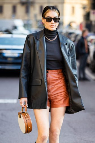 MILAN, ITALY - FEBRUARY 22: Brittany Xavier, wearing a black turtleneck top, black leather blazer, brown leather shorts, black boots and beige bag, is seen outside Salvatore Ferragamo show, during Milan Fashion Week Fall/Winter 2020-2021 on February 22, 2020 in Milan, Italy. (Photo by Claudio Lavenia/Getty Images)