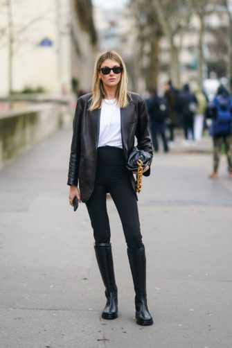 PARIS, FRANCE - FEBRUARY 26: Camille Charriere wears Ray-Ban sunglasses, a black leather jacket, a white t-shirt, a Bottega Veneta leather bag with a golden chain handle, black pants, black leather high boots, outside Mugler, during Paris Fashion Week - Womenswear Fall/Winter 2020/2021, on February 26, 2020 in Paris, France. (Photo by Edward Berthelot/Getty Images)