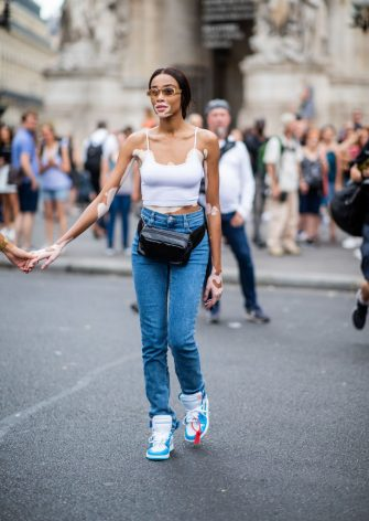 PARIS, FRANCE - JULY 02: Winnie Harlow wearing denim jeans, belt bag, white top is seen outside Schiaparelli on day two during Paris Fashion Week Haute Couture FW18 on July 2, 2018 in Paris, France. (Photo by Christian Vierig/Getty Images)