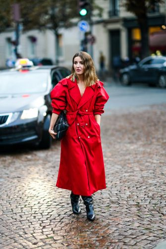 PARIS, FRANCE - SEPTEMBER 29: Alexandra Pereira wears a red trench coat / dress, a black leather quilted bag, black shiny leather boots, outside Koche, during Paris Fashion Week - Womenswear Spring Summer 2021 on September 29, 2020 in Paris, France. (Photo by Edward Berthelot/Getty Images)