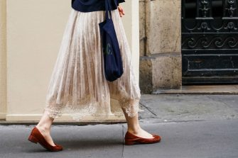 PARIS, FRANCE - JUNE 20: A passerby wears a pale pink pleated skirt with embroidery, brown flat shoes, a blue bag, on June 20, 2020 in Paris, France. (Photo by Edward Berthelot/Getty Images)