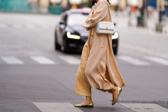 PARIS, FRANCE - JULY 04: A passerby wears yellow checked wool knitted pants, golden flat ballerina shoes, a white Chanel bag, a salmon-pink flowing long coat, on July 04, 2020 in Paris, France. (Photo by Edward Berthelot/Getty Images)
