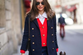 PARIS, FRANCE - MARCH 19: Therese Hellström wears Ray-Ban sunglasses, a white shirt with Peter Pan collar, a navy dark blue oversized military wool jacket with golden buttons, a red wool cardigan with golden heart-shaped buttons, a brown leather Hermes bag, blue denim jeans, on March 19, 2021 in Paris, France. (Photo by Edward Berthelot/Getty Images)