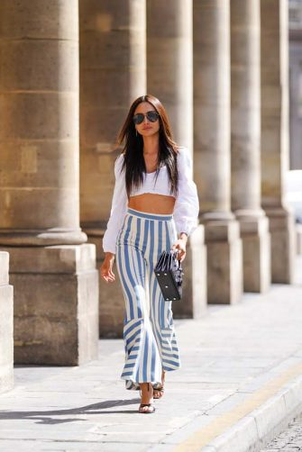 PARIS, FRANCE - JULY 09: Patricia Gloria Contreras wears a white cropped top with puff sleeves from Lovers and Friends, blue and white striped and flared pants from Odi Odi, heels shoes from Raye de Label, a black leather crocodile pattern bag from Saint Laurent YSL, on July 09, 2020 in Paris, France. (Photo by Edward Berthelot/Getty Images)