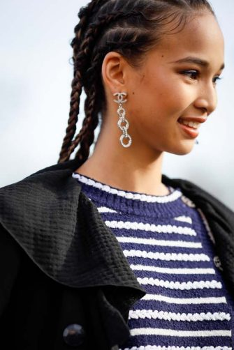 PARIS, FRANCE - MARCH 03: A guest wearing Chanel earrings, stripe shirt, white mini skirt, black coat and Chanel bag outside the Chanel show during Paris Fashion Week Womenswear Fall/Winter 2020/2021 Day Nine on March 03, 2020 in Paris, France. (Photo by Hanna Lassen/Getty Images)