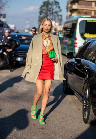 MILAN, ITALY - FEBRUARY 19: Leonie Hanne is seen wearing camel blazer, green Bottega bag, red mini skirt, blouse with print, green heels outside Alberta Ferretti during Milan Fashion Week Fall/Winter 2020-2021 on February 19, 2020 in Milan, Italy. (Photo by Christian Vierig/Getty Images)