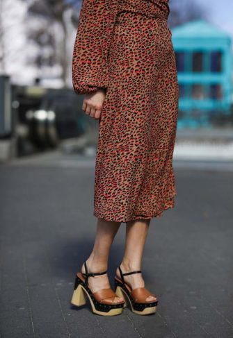 HAMBURG, GERMANY - MARCH 30: Anna Wolfers poses wearing camel and red leo midi wrap dress and wooden sole heels on March 30, 2021 in Hamburg, Germany. (Photo by Jeremy Moeller/Getty Images)
