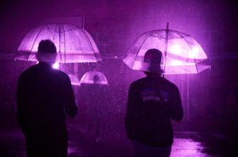 PARIS, FRANCE - AUGUST 02: Visitors stand with umbrellas at the 'Purple Rain' installation at the Lycée Jacques-Decour on August 02, 2020 in Paris, France. Part of Festival Paris l'Eté, the installation by Pierre Ardouvin is a tribute to the song by Prince and allows visitors to role play while equipped with umbrellas and accompanied by the song. (Photo by Kiran Ridley/Getty Images)
