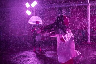 PARIS, FRANCE - AUGUST 02: A woman dances at the 'Purple Rain' installation at the Lycée Jacques-Decour on August 02, 2020 in Paris, France. Part of Festival Paris l'Eté, the installation by Pierre Ardouvin is a tribute to the song by Prince and allows visitors to role play while equipped with umbrellas and accompanied by the song. (Photo by Kiran Ridley/Getty Images)