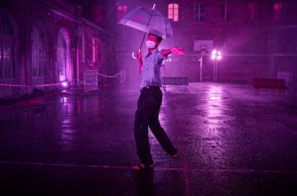 PARIS, FRANCE - AUGUST 02: A visitor dances at the 'Purple Rain' installation at the Lycée Jacques-Decour on August 02, 2020 in Paris, France. Part of Festival Paris l'Eté, the installation by Pierre Ardouvin is a tribute to the song by Prince and allows visitors to role play while equipped with umbrellas and accompanied by the song. (Photo by Kiran Ridley/Getty Images)
