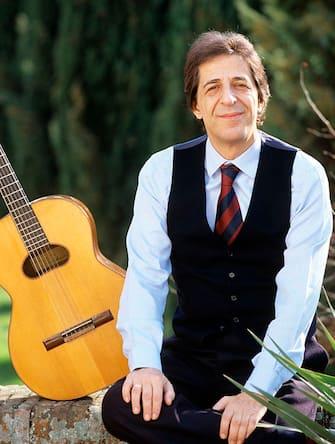 The Italian singer-songwriter and actor Giorgio Gaber (Giorgio Gaberscik) posing smiling with his guitar. 1982 (Photo by Angelo Deligio/Mondadori via Getty Images)