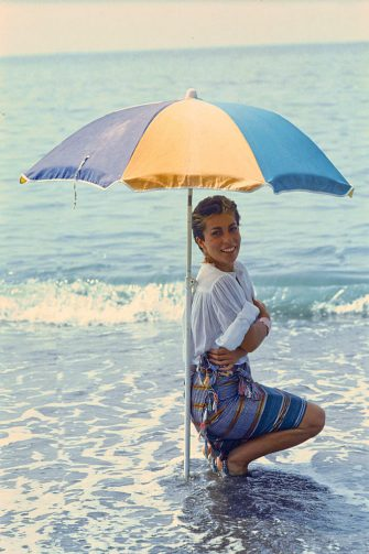Italian singer-songwriter Giuni Russo posing smiling crouching under a beach umbrella o the seashore. 1982 (Photo by Angelo Deligio/Mondadori via Getty Images)