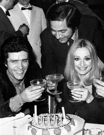 Dancer and presenter Raffaella Carrà celebrating her birthday with a cake and candles in front of her and toasting with Gianni Nazzaro, Corrado and Gianni Boncompagni. Saint Vincent, 1972. (Photo by Angelo Deligio\Mondadori Portfolio by Getty Images)