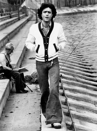 The Italian singer Giovanni Nazzaro (known as Gianni Nazzaro) walking along the canals of Milan and wearing casual clothes: bell-bottom jeans and buttons sweat. Milan (Italy), 1974.. (Photo by Mondadori via Getty Images)