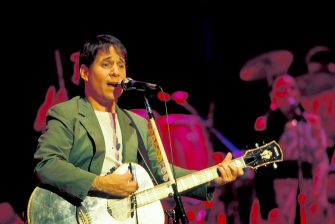 American musician Paul Simon plays guitar during the tour in support of his 'Graceland' album on stage at the Jones Beach Theatre, Wantagh, New York, July 6, 1987. (Photo by Jack Vartoogian/Getty Images)