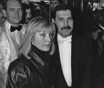 Singer Freddie Mercury (1946 - 1991) of British rock band Queen with his friend Mary Austin at an after-party in London for 'Dave Clark's Time - The Musical', 9th April 1986. Behind them is Queen's manager Jim Beach, . (Photo by Dave Hogan/Getty Images)