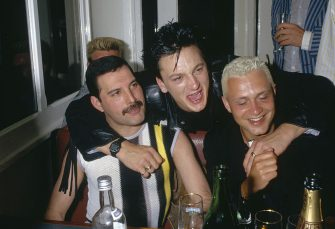 Singer Freddie Mercury is embraced by fellow musician Mark o'Toole (Frankie Goes to Hollywood) while sitting with musician Belouis Some (right), 1986. (Photo by Dave Hogan/Getty Images)
