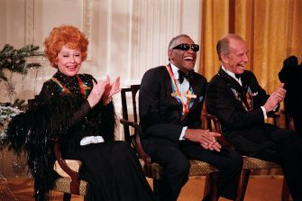 (Original Caption) 12/7/1986-Washington, D.C.-: Lucille Ball and Ray Charles laugh at remarks made by President Reagan at the White House in an East Room ceremony for the Kennedy Center Honors.