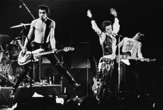 SAN FRANCISCO, CA - 1978:  Punk singer Johnny Rotten (with his hands in the air) and bassist Sid Vicious, of legendary The Sex Pistols, perform onstage during the band's last 1978 public appearance at the Winterland Ballroom in San Francisco, California. Guitarist Steve Jones is on the right. (Photo by George Rose/Getty Images)