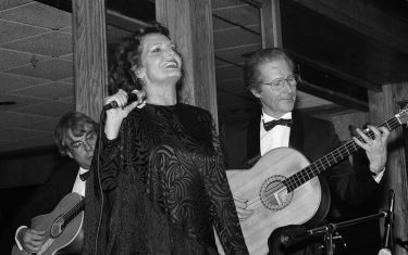 Portuguese Fado singer Amalia Rodrigues (1920 - 1999) performs on stage, Newark, New Jersey, November 28, 1987. The guitarists performing with her are unidentified. (Photo by Rita Barros/Getty Images)