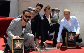 epa03673225 US band Backstreet Boys touch their star during a ceremony honoring them on the Hollywood Walk of Fame in Hollywood, California, USA, 22 April 2013.  The Backstreet Boys are a multi-platinum pop group that started 20 years ago and have sold more than 130 million albums worldwide. From L to right are:  AJ McLean, Howie Dorough, Kevin Richardson, Nick Carter and Brian Littrell.  EPA/MICHAEL NELSON