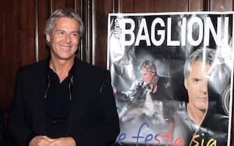Claudio Baglioni davanti alla locandina di un suo concerto