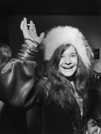 circa 1969:  American rock singer Janis Joplin (1943 - 1970) smiles and waves with a cigarette in one hand and a drink in the other  while attending a party. She wears a fur hat.  (Photo by Walter Daran/Hulton Archive/Getty Images)