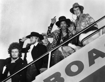 1968:  Jimi Hendrix and Mitch Mitchell of The Jimi Hendrix Experience wave goodbye as they board an aeroplane at London Airport, with assorted members of the Byrds, the Soft Machine and the Alan Price Set.  (Photo by J. Wilds/Keystone/Getty Images)