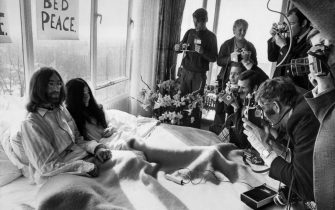 Beatles member John Lennon (L) and his wife Yoko Ono receive journalists 25 March 1969 in the bedroom of the Hilton hotel in Amsterdam, during their honeymoon in Europe. AFP / ANP PHOTO (Photo credit should read /AFP via Getty Images)