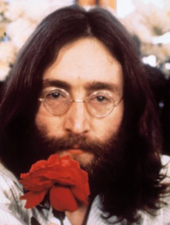 """(Original Caption) Head shot of Beatle John Lennon with rose during the """"Bed-in for Peace"""" demonstration. (Photo by Bettmann via Getty Images)"""