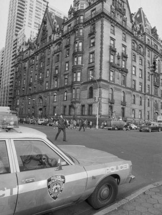 (Original Caption) Police direct traffic outside the Dakota, an apartment house, December 9th, the morning after former Beatle John Lennon was shot to death in front of the building. Police say Lennon was shot by a deranged man who had been stalking him for days.