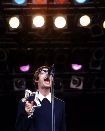 Liam Gallagher performs on stage with Oasis at Glastonbury Festival, United Kingdom, 1994. (Photo by Martyn Goodacre/Getty Images)