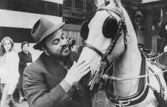 Italian opera singer Luciano Pavarotti calming the horse before taking a horse and carriage ride from his hotel to Liberty's, outside the Savoy Hotel in London, May 14th 1981. (Photo by Graham Turner/Keystone/Getty Images)