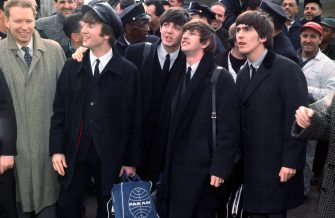John Lennon, Paul McCartney, Ringo Starr, and George Harrison (L-R) arrive at Idlewild Airport to the sight and sound of several hundred cheering fans who have gathered to greet the Fab Four.