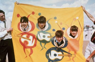 The Beatles poke smiling faces out of a banner drawn with beatle bodies holding guitars in the early part of their band's career.