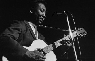 American blues singer and guitarist Muddy Waters (1913 - 1983) performs at the American Folk Blues Festival in London, 1963. (Photo by Tony Evans/Getty Images)