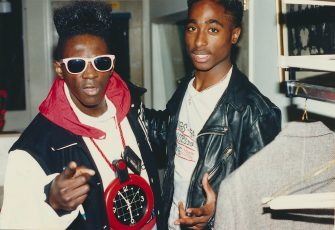 Flavor Flav, standing with rapper Tupac Shakur, greets fans backstage during the 1989 American Music Awards, Los Angeles, California, January 30, 1989. (Photo by Clarence Gatson/Gado/Getty Images)