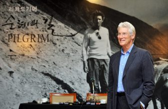 """US actor Richard Gere (R) poses for a photo session before a press conference for an exhibition of his photos in Seoul on June 22, 2011. Gere, a Buddhist and longtime campaigner for the rights of Tibetans, voiced concern at what he called torture and killing in Tibet, during a visit to South Korea to promote an exhibition of photos he took in Tibet and other Buddhist-related sites, called """"Pilgrim"""".  AFP PHOTO/JUNG YEON-JE (Photo credit should read JUNG YEON-JE/AFP via Getty Images)"""
