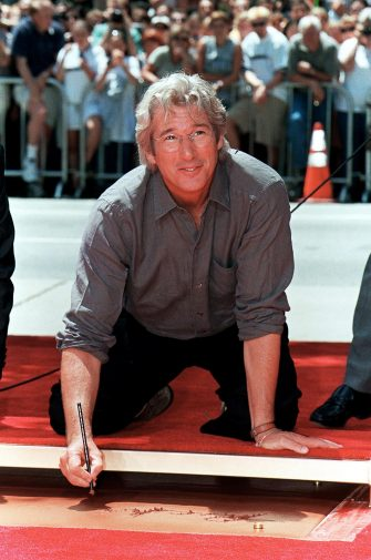 """HOLLYWOOD, :  US actor Richard Gere signs his name before placing his hands and feet in cement during a ceremony 26 July 1999 at Mann's Chinese Theatre in Hollywood, Ca.  Gere, who has starred in films such as """"Pretty Woman"""", """"Officer and a Gentleman""""  and """"Red Corner"""", is currently featured with Julia Roberts in the romantic-comedy """"Runaway Bride.""""  AFP PHOTO/Vince BUCCI (Photo credit should read Vince Bucci/AFP via Getty Images)"""