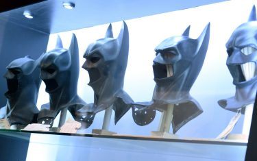 A visitor looks at Batman masks used in the seven Batman films at The Batman Exhibit on the exhibitions opening day on the Warner Bros. VIP Studio Tours at the Warner Bros. Studio lot in Burbank, California, on June 26, 2014. The exhibit celebrates the DC Comics iconic super hero and features batmobiles, costumes, props and other items from all seven Batman movies.    AFP PHOTO / Robyn Beck        (Photo credit should read ROBYN BECK/AFP via Getty Images)