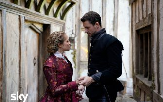 These images are under embargo until w/c 11th January  In the present day, Domenico finds a brutalised body in Oxford and suspects a mysterious affliction called blood rage has returned. In 1590, Matthew is forced to beg forgiveness from Father Hubbard for executing Tom Caldwell – the sort of conflict he had hoped to avoid. Diana and Matthew are introduced to John Dee by Mary Sidney. They explore his library, hoping to find clues to the whereabouts of the Book of Life. Dee tells them his scryer Edward Kelley stole a valuable book from him and is now hiding in Bohemia, and Matthew and Diana suspect it must be the Book of Life. Goody Alsop teaches Diana about weaving and knots, and Diana is overwhelmed to discover a new world of magic open up to her. In the present, Em practises higher magic to try and reach Diana's mother, Rebecca, in order to help her niece get closer to the Book. Matthew suspects that Kit has betrayed Diana's identity to Cecil. A cautious Matthew and Diana meet with Queen Elizabeth I, who accuses Matthew of betraying her by marrying Diana. As a test of loyalty, she orders them to bring Edward Kelley home from the clutches of King Rudolf, so that she can claim the Philosopher's Stone, the secret to eternal life which Kelley had promised. Before they can leave however, Gallowglass arrives with a message from Matthew's father Philippe – summoning Matthew and Diana to France.