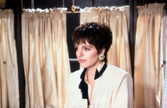 Liza Minnelli standing in front of curtains in a scene from the film 'Arthur 2: On the Rocks', 1988. (Photo by Warner Brothers/Getty Images)