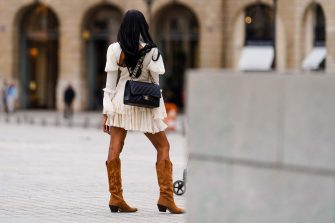 PARIS, FRANCE - JULY 04: A passerby wears a white ruffled lace pleated dress, a black leather quilted Chanel bag, brown suede high cow-boy pointy boots, on July 04, 2020 in Paris, France. (Photo by Edward Berthelot/Getty Images)