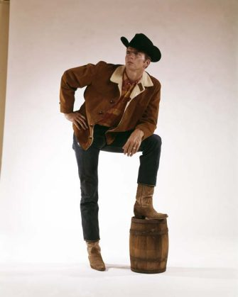 Portrait of a man in a cowboy outfit as he stand with one boot on a small barrel, 1965. (Photo by Camerique/Getty Images)