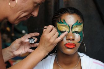"A make-up artist prepares a dancer of the ""comparsa"" C1080 for her performance in the Llamadas in Montevideo on February 8 2008. The Llamadas are a part of the carnival festivities that originated from the Afro-Uruguayan community and unites dancers, drummers and spectators for a parade in the neighbourhoods of Palermo and Barrio Sur. AFP PHOTO / Pablo Porciuncula (Photo by Pablo PORCIUNCULA / AFP) (Photo by PABLO PORCIUNCULA/AFP via Getty Images)"